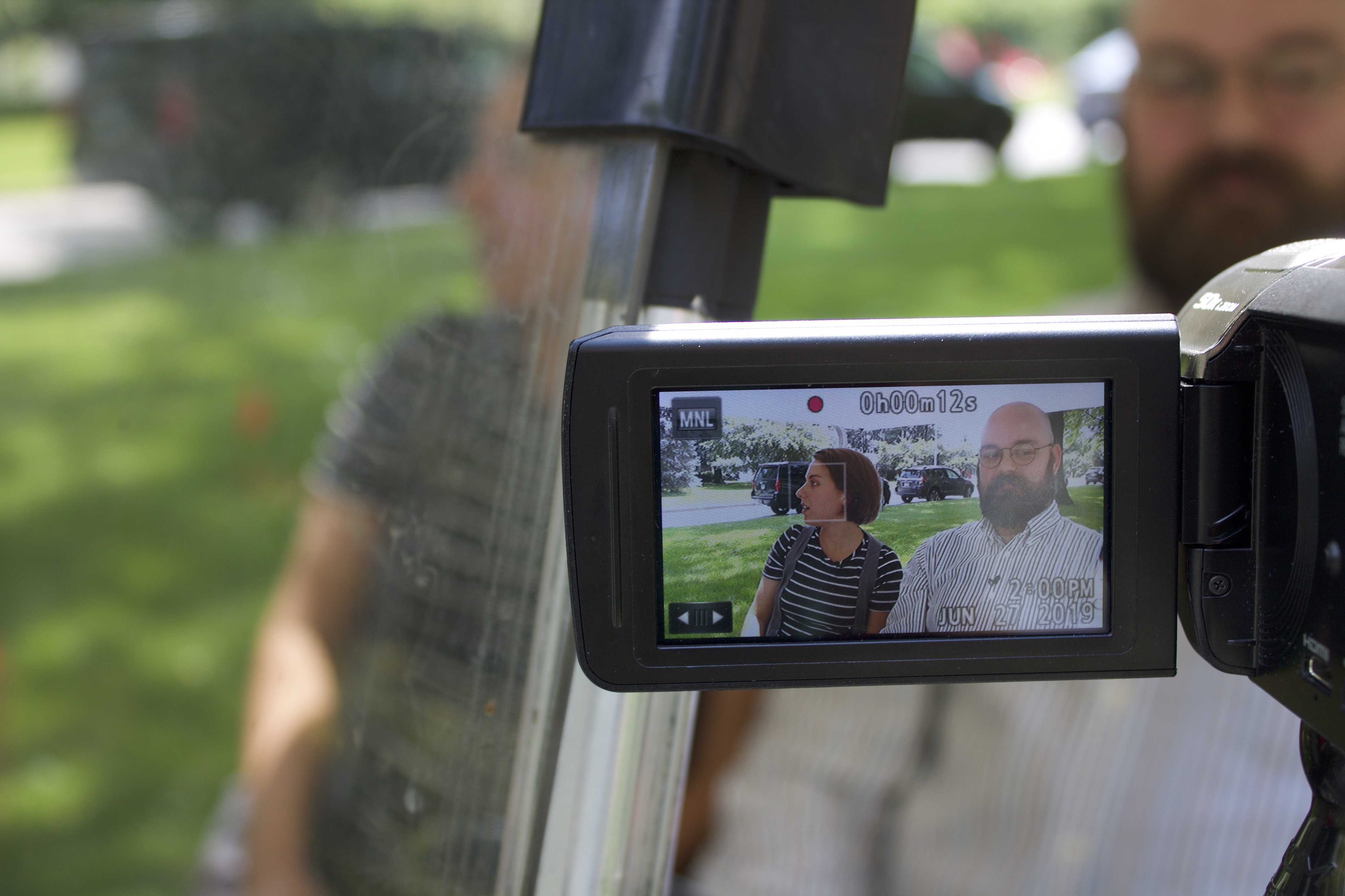 Image for Episode filming in progress: while Jess and Tony converse in a moving golf cart, members of the production team capture the filming underway in the camera