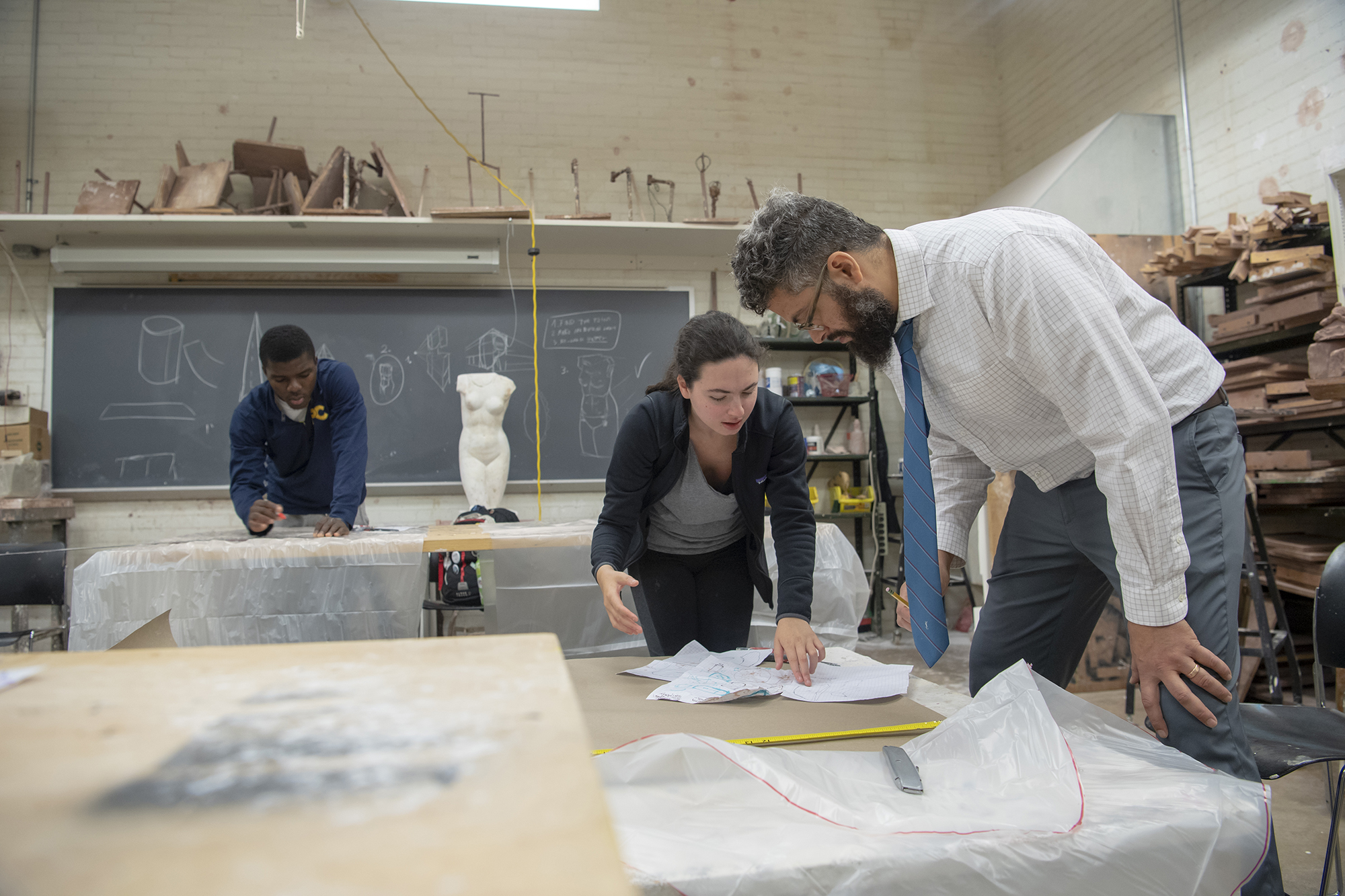 Image for Sculpture Professor Frederick Wright Jones consults with a student in a studio art class. Our faculty exhibit nationwide, and their own experiences provide insight for students who wish to pursue careers in artistic fields.